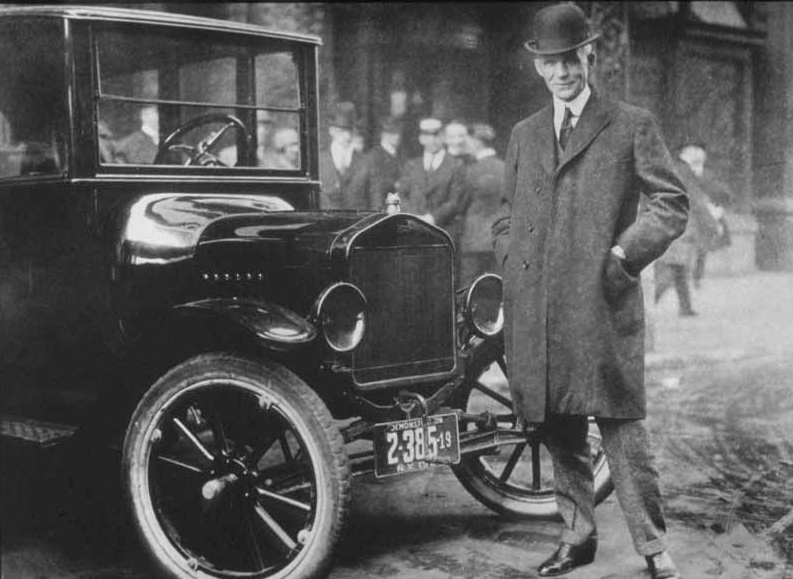 henry ford, founder of ford motor company, standing next to a ford car. ulmer