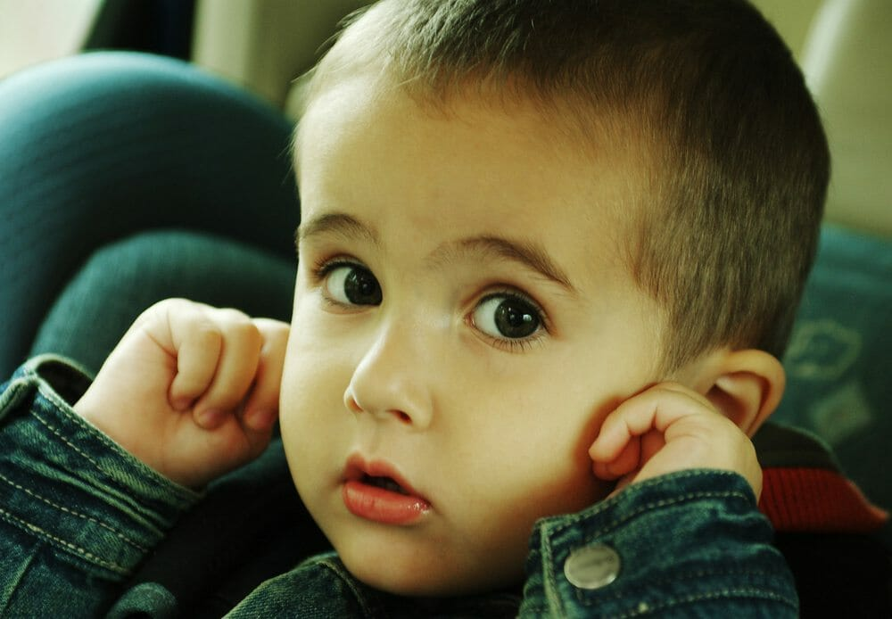 child covering ears in car because of vehicle sounds