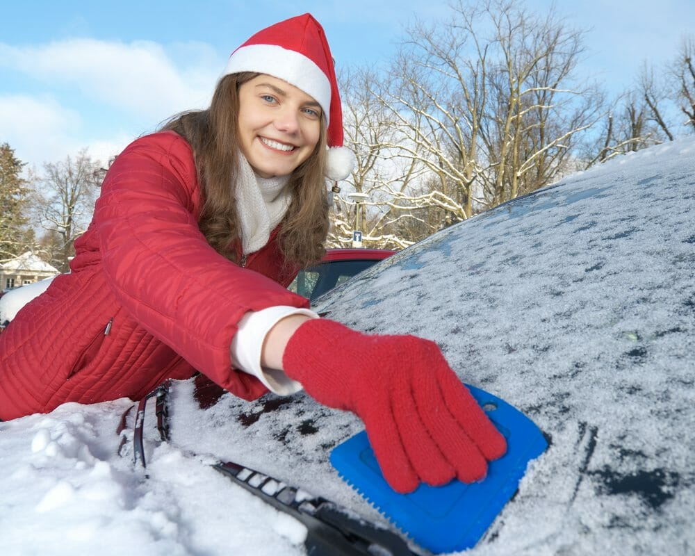 Santa hat scraping snow off car - safe holiday travel tips